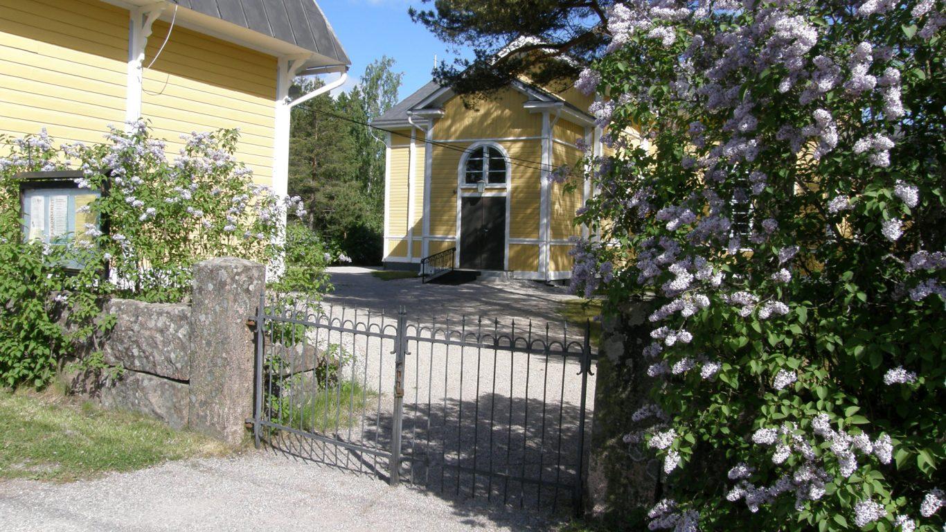 Kuusjoen kirkko alkukesällä syreenin kukkiessa