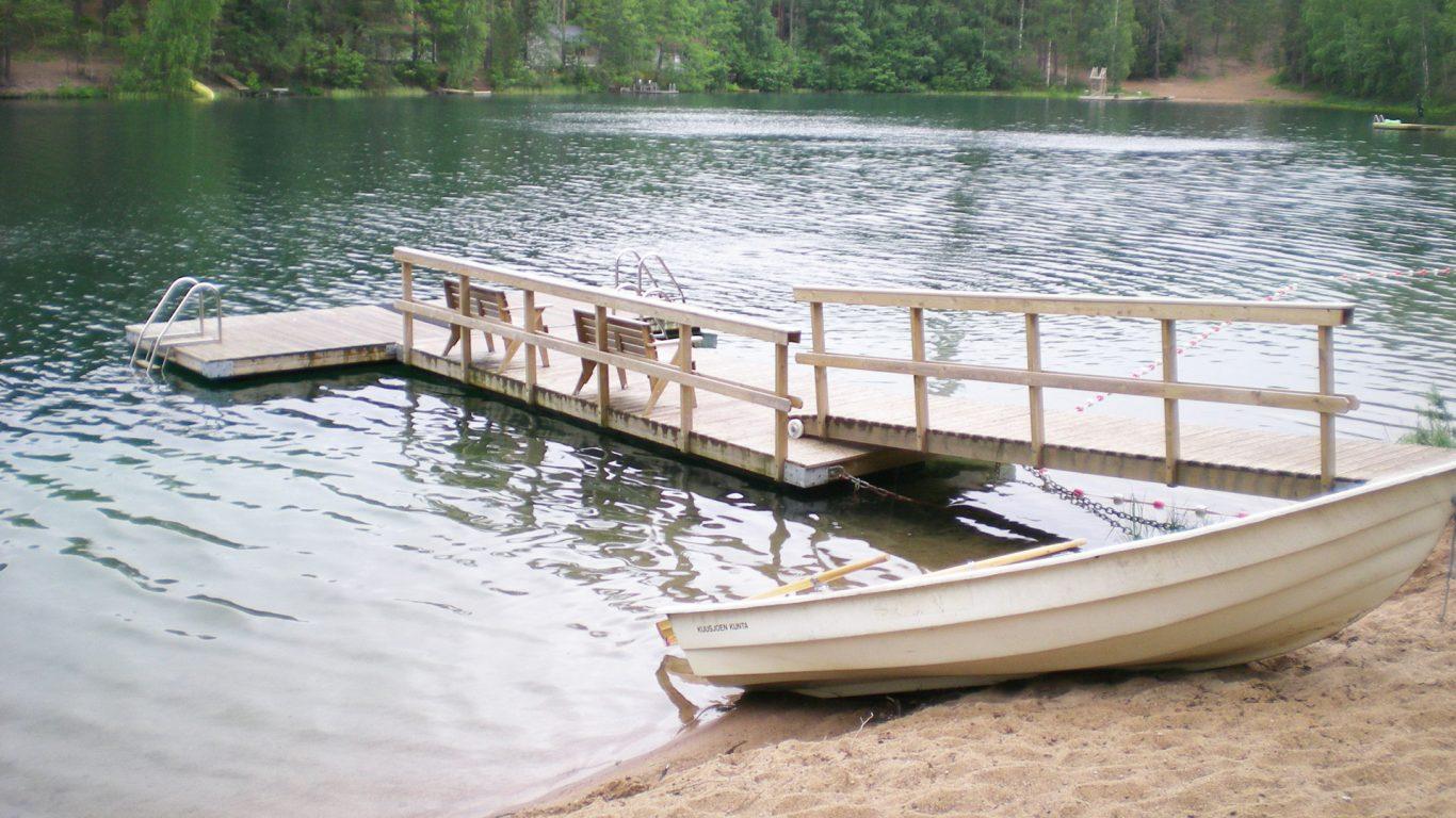 Nummijärven uimaranta, kirkasvetinen järvi, laituri ja vene.