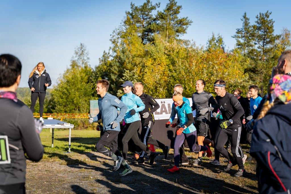 Teijo Uphill Challenge -tapahtuman lähtöviivan tunnelmia, iloisia juoksijoita lähdössä esteradalle, juontaja seisoo lavalla