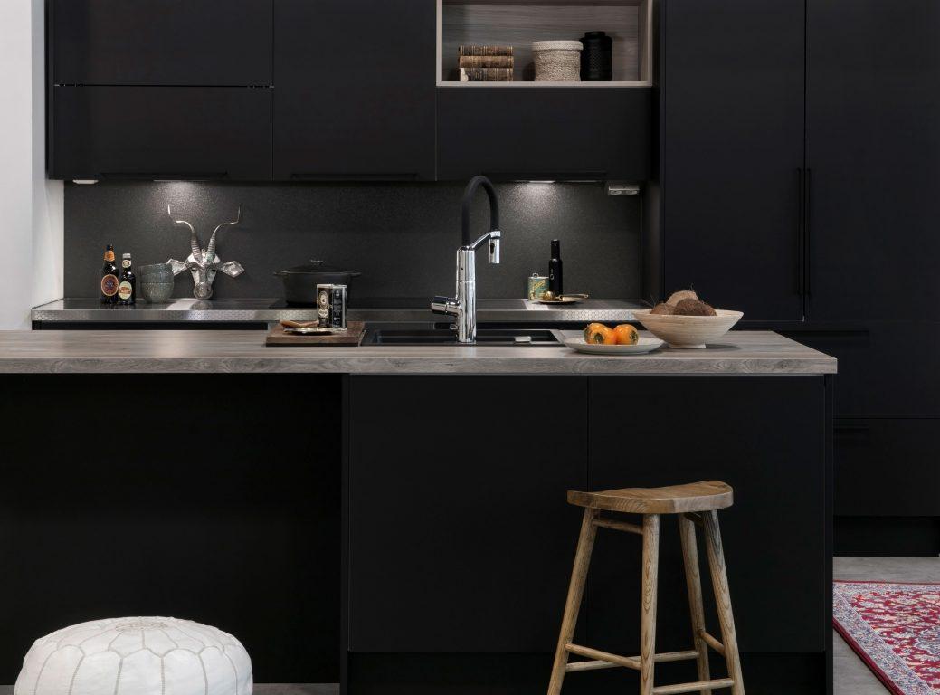 Musta keittiö puunsävyisillä tasoilla