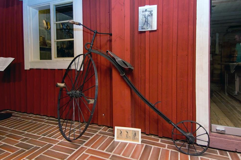 Pyörä, jossa on iso etupyörä ja pieni takapyörä. Vanhanaikainen.