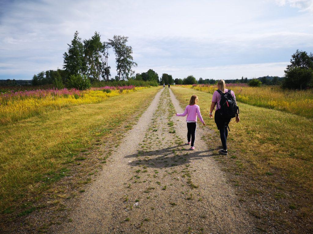 Äiti ja tytär kävelevät esteettömällä polulla.
