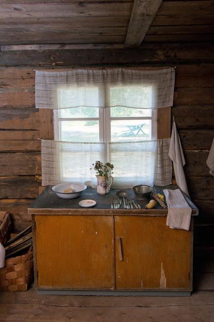 Kuva vanhan rakennuksen keittiöstä, pöytä, keittiöesineitä.