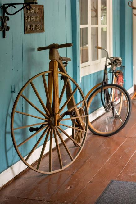Museorakennuksen lasiveranta. Seinään nojaa vanha puinen pyörä, jossa on iso etupyörä ja pieni takapyörä.