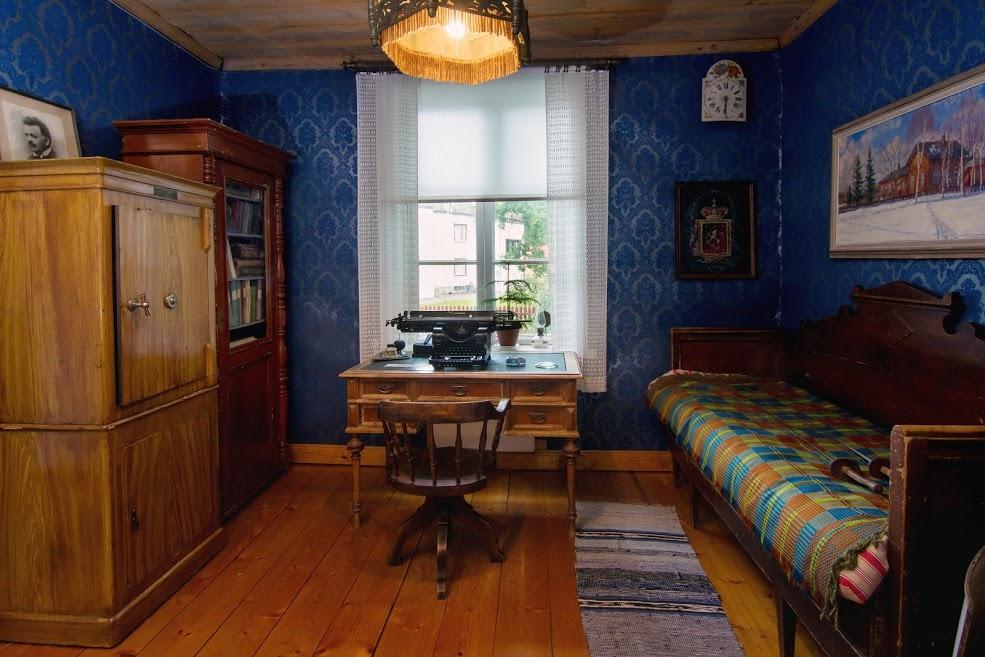 Museon sali, siniset tapetit, vanha kirjoituspöytä ja kirjoituskone. Puusohva.