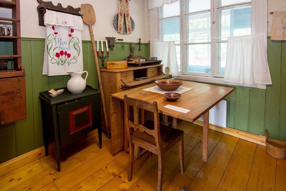Vanhanaikainen keittiö. Pöytä, kaappeja, kirjottu liina, vanhoja keittiöesineitä.