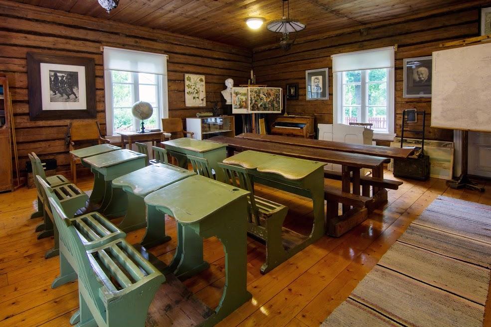 Vanhanaikainen luokkahuone. Vihreät paripulpetit ja opetukseen käytettyä havaintomateriaalia.