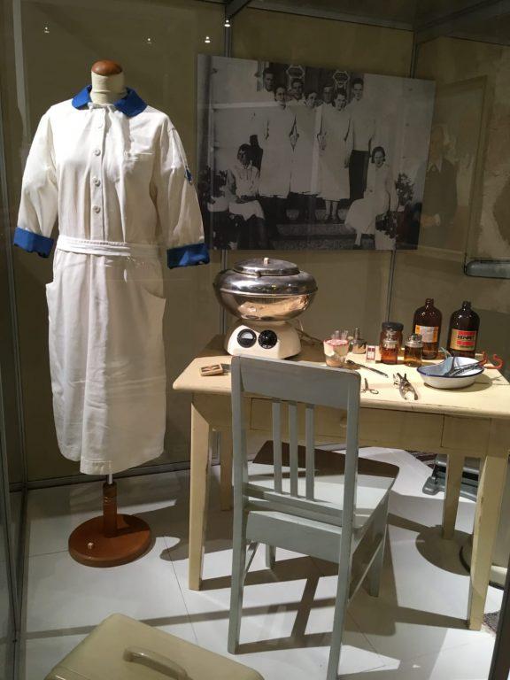 Sairaanhoitajan puku, hoitajan pulpetti, lääkepulloja, painelaite, mittausastioita, seinällä valokuva