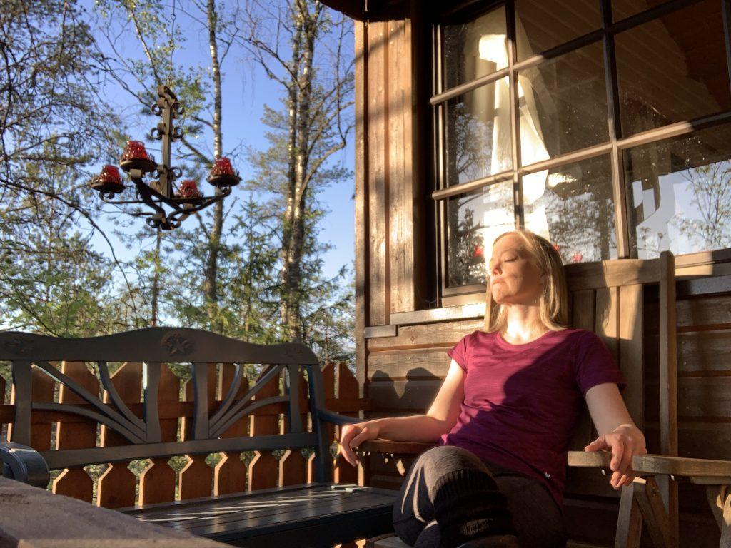nainen nauttii auringonlaskusta mökin terassilla