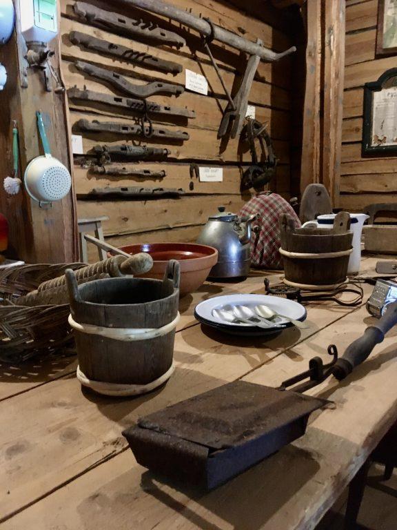 Vanhoja esineitä museossa Suomusjärvellä. Kotitalouteen liittyviä esineitä. Tiinu, lautasia, ruuanlaittovälineitä.