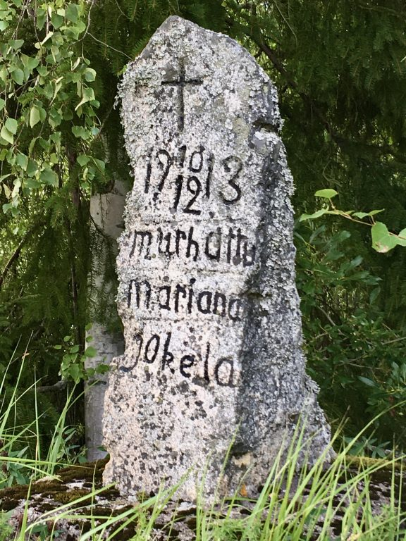 Kivestä veistetty muistomerkki, jossa tekstiä ja risti.
