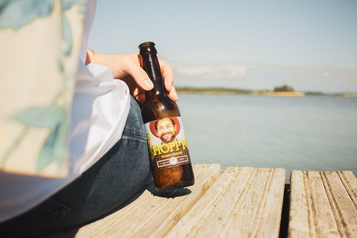 Lepolan Hoppy-humalasiideri auringonpaisteessa laiturilla istuvan henkilön kädessä, taustalla siintää meri.