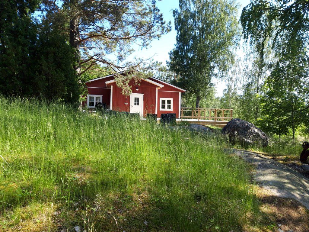 Punavalkoinen Lilla Lönnviken alkukesän vehreyden keskellä