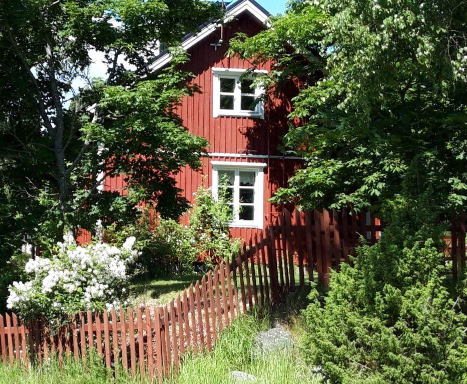 Punavalkoinen Villa Lönnviken suurten lehtipuidenympäröimänä