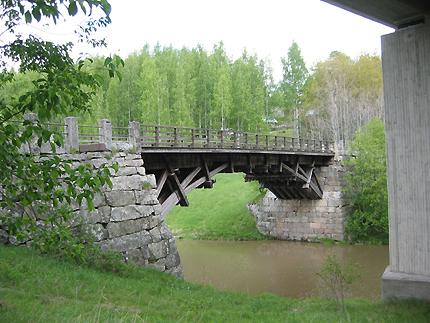 Vanha puinen silta kesäisessä maisemassa. Puut vihertävät.
